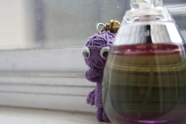 A small crying voodoo doll on a window sill next to a perfume bottle