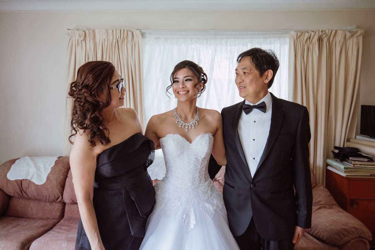 A woman in a white strapless wedding dress standing between her mum and dad, dressed in a black dress and a black suit, respectively. They are looking at each other