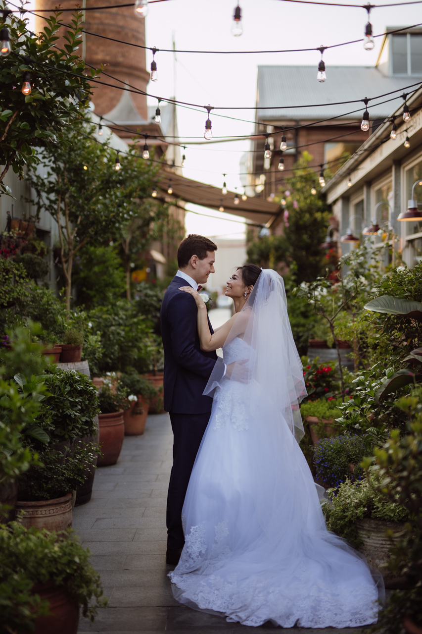 Side view of a bride and groom embracing and looking at each other. They are in a garden setting