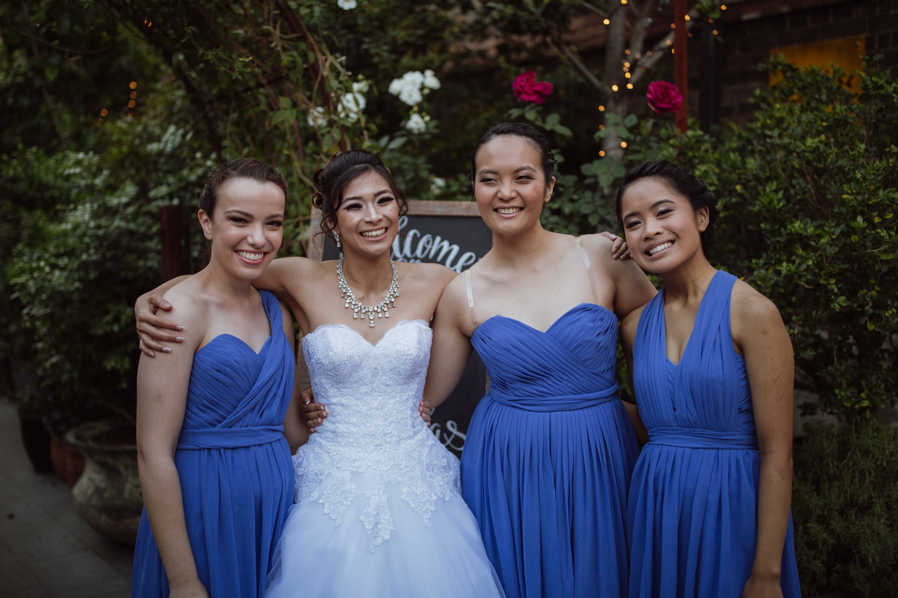A bride in a white strapless dress with three bridesmaids in blue dresses