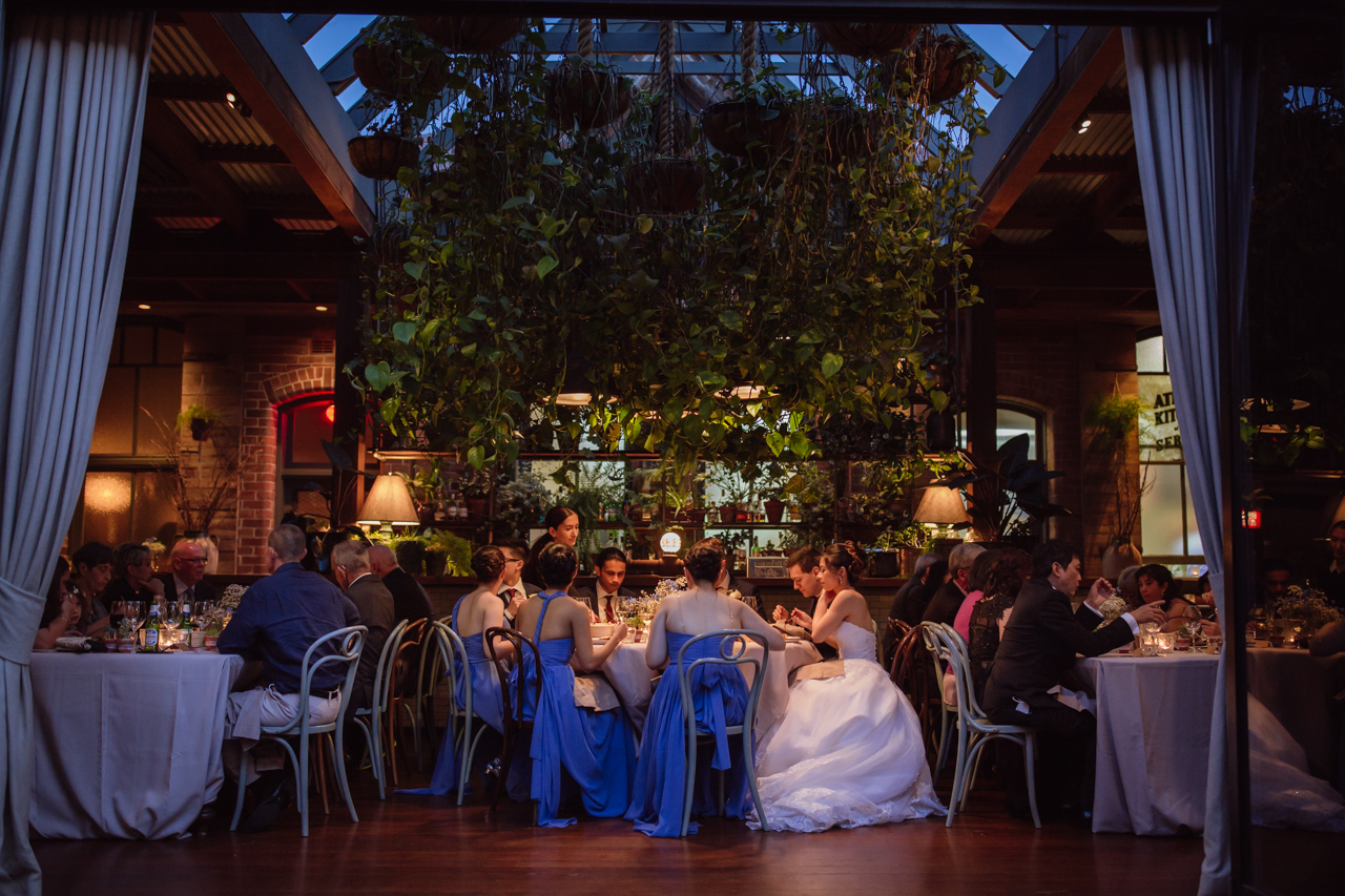 A view inside a wedding reception venue. The bridal party can be seen centre of frame