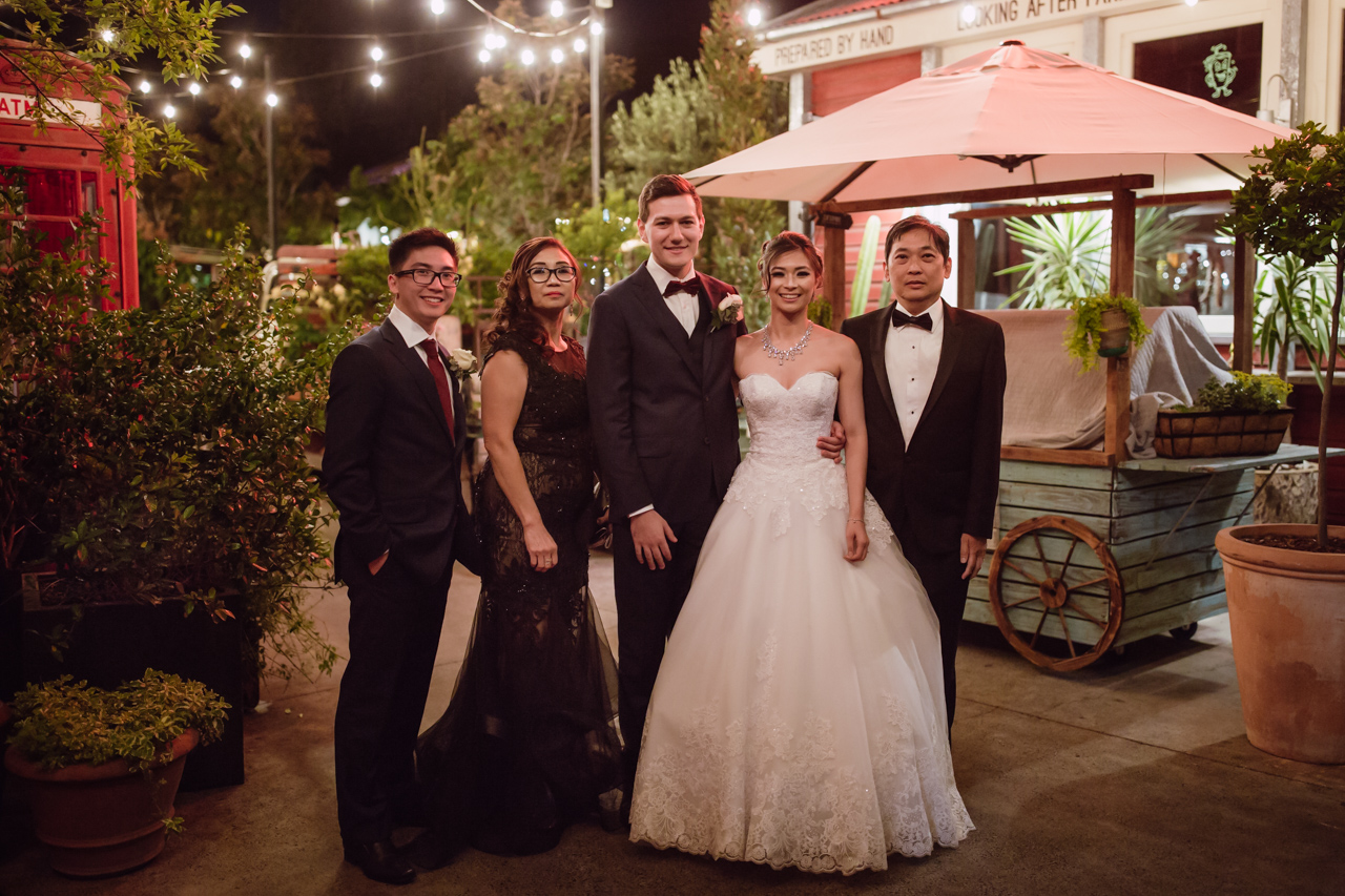 A married couple, the groom in a navy suit and the bride in a white ballgown, along with the bride's family – mum, dad, and brother. It's evening and they are outside in a garden-like setting