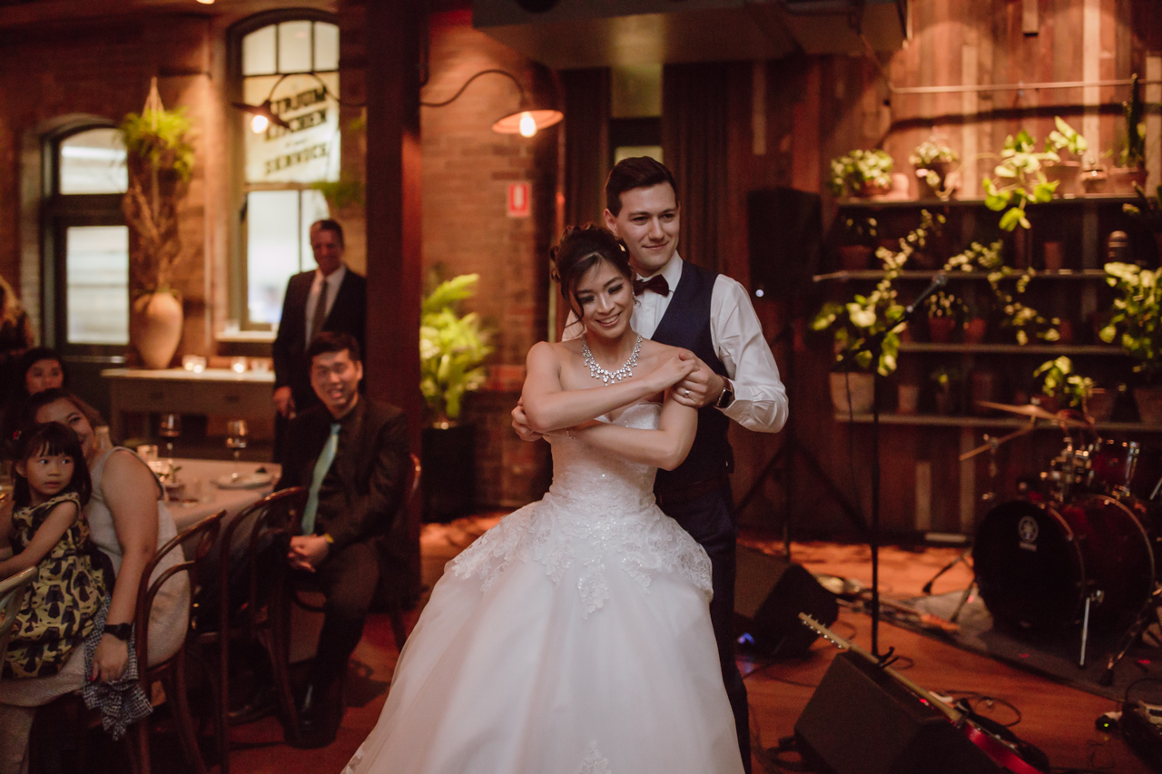 A married couple dancing in a room. Some wedding guests look on from the side. There are some musical instruments and microphones set up in the background