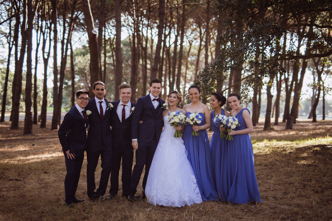 A bride and groom and bridal party standing close together and smiling/laughing