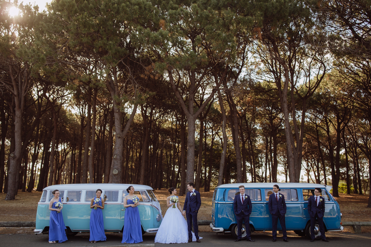 A bride and groom and their bridal party in front of two camper vans
