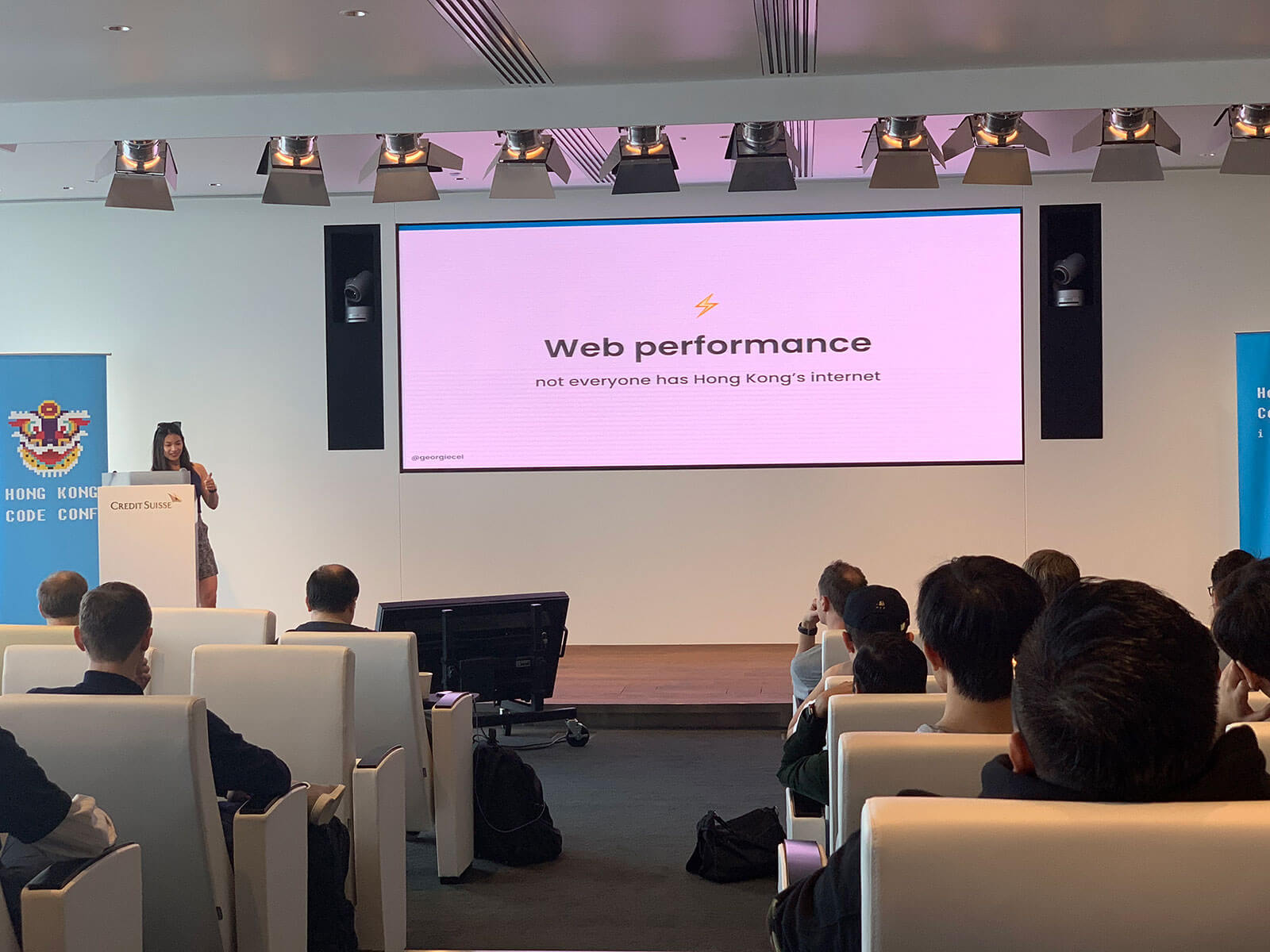 "A conference room with white chairs with people seated in them. At the front of the room on a stage is a woman standing at a podium. The screen backdrop on the stage reads ""Web Performance�"