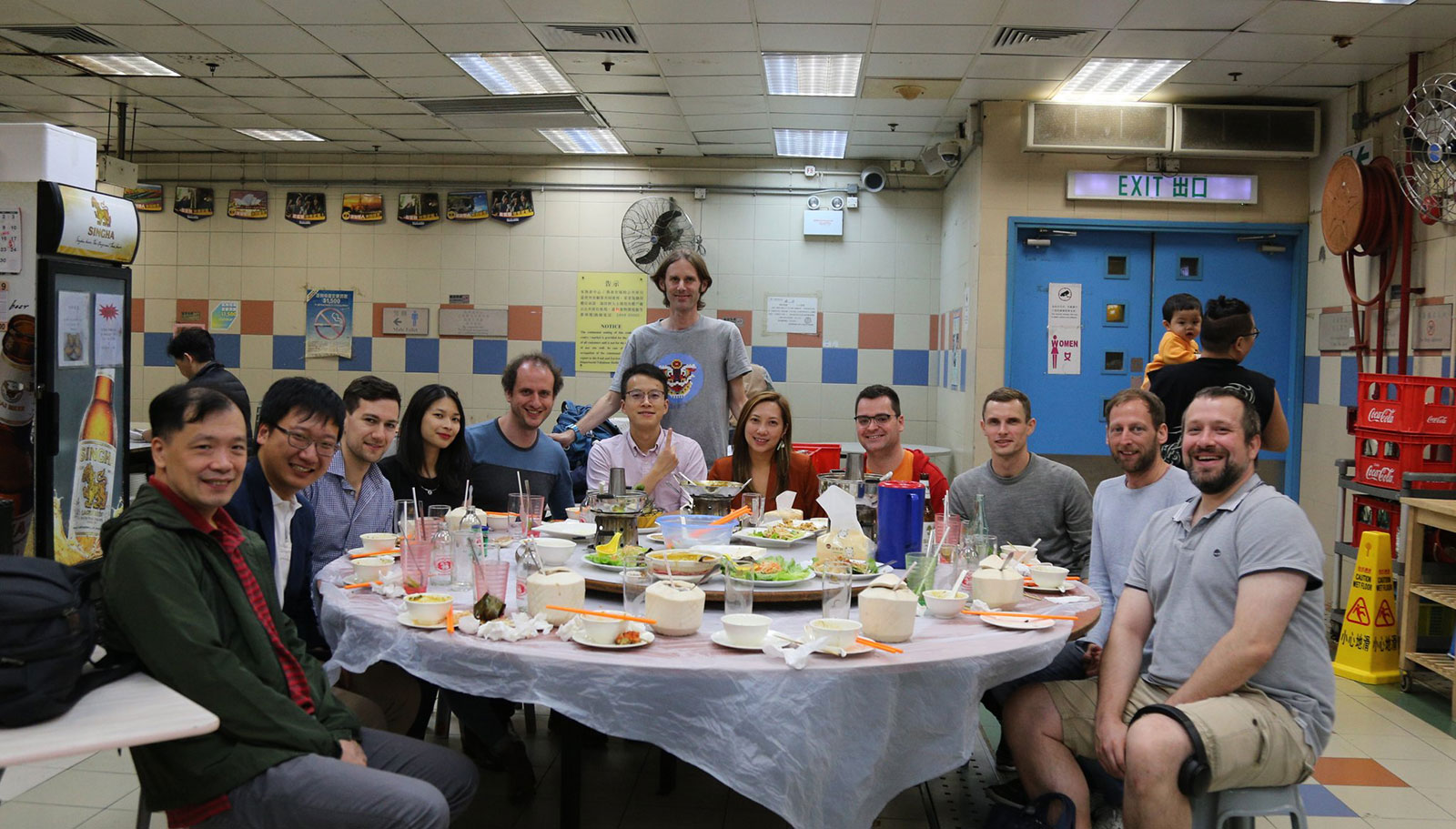 A group of people around a round table, smiling. The table has food on it and the setting is inside a food court.