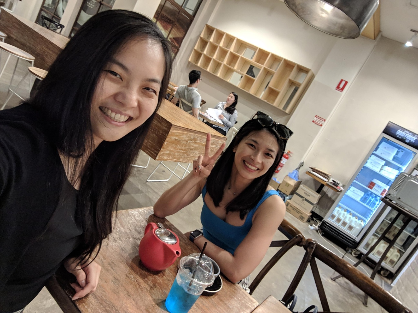 A selfie with two women in it; both are smiling. The woman taking the selfie is wearing black and the other woman is wearing blue. They are seated in a cafe and on the table is a pot of tea and a plastic cup of blue lemonade.