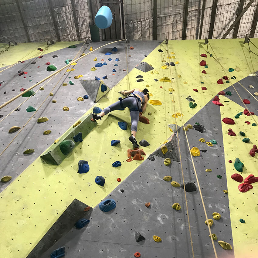 A woman wearing blue leggings and a sports bra climbing an indoor rock climbing wall, facing the wall. She has her feet on orange holds and there are many different coloured holds on the wall, which is grey and yellow.