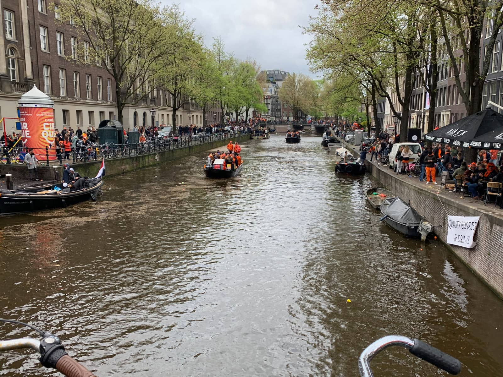 A canal river as seen from a perpendicular bridge. There are several bits of people wearing orange and celebrating, and the banks are also filled with people wearing orange