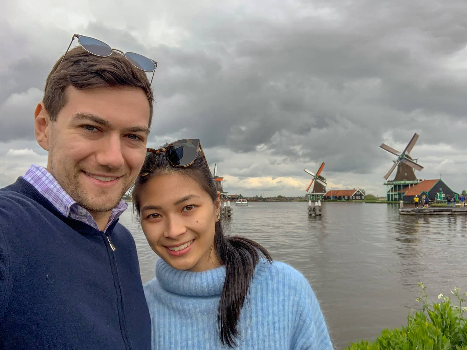 A man and woman taking a selfie in front of a river with Dutch windmills in the background. It is a very cloudy day
