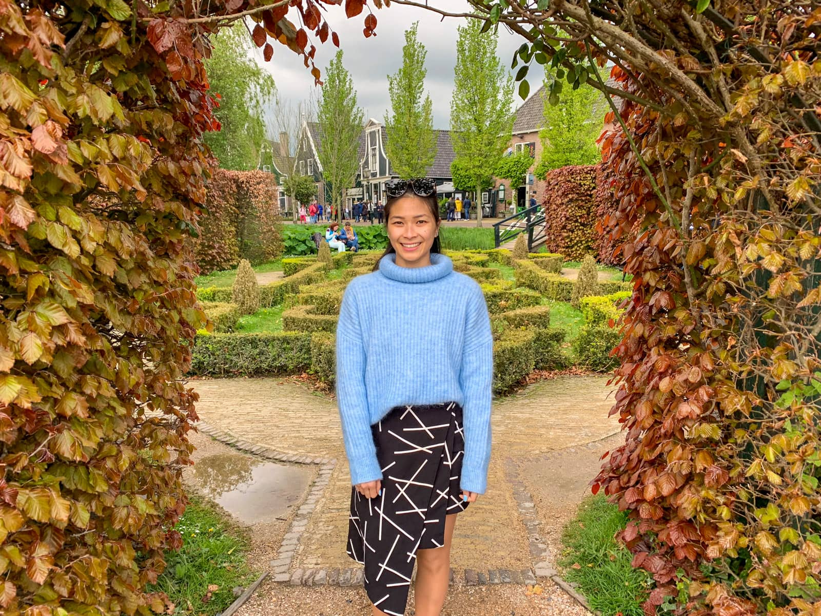 A woman in a blue sweater and black patterned skirt under an hedge arch of red and yellow coloured leaves. In the background is a small green garden maze.