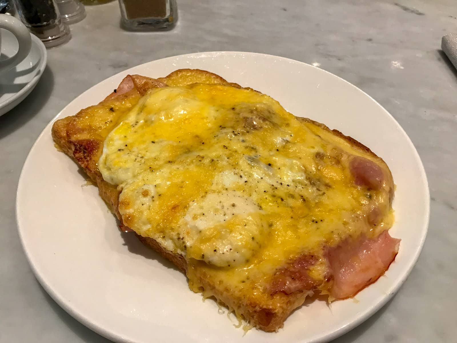 A white plate with fried eggs, cheese and ham toasted on it.