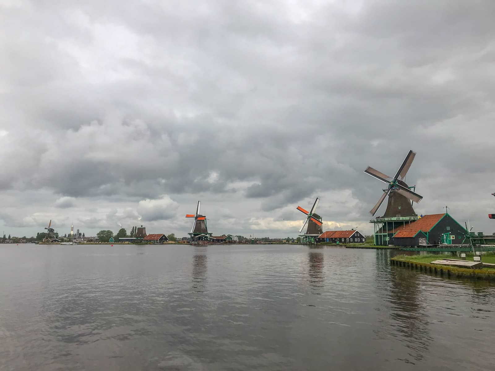Several windmills spread out across land, seen from the opposite side of a river