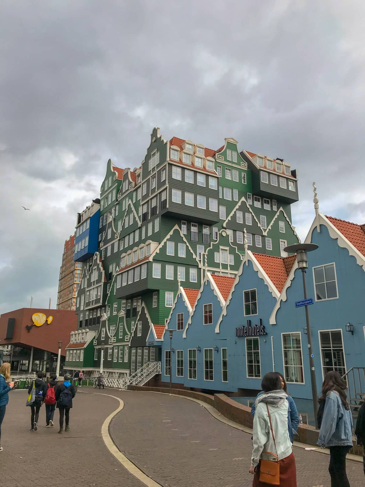 An interestingly-architectured building resembling little houses put together, in colours of green, blue, and blue-grey. The sky is very grey.