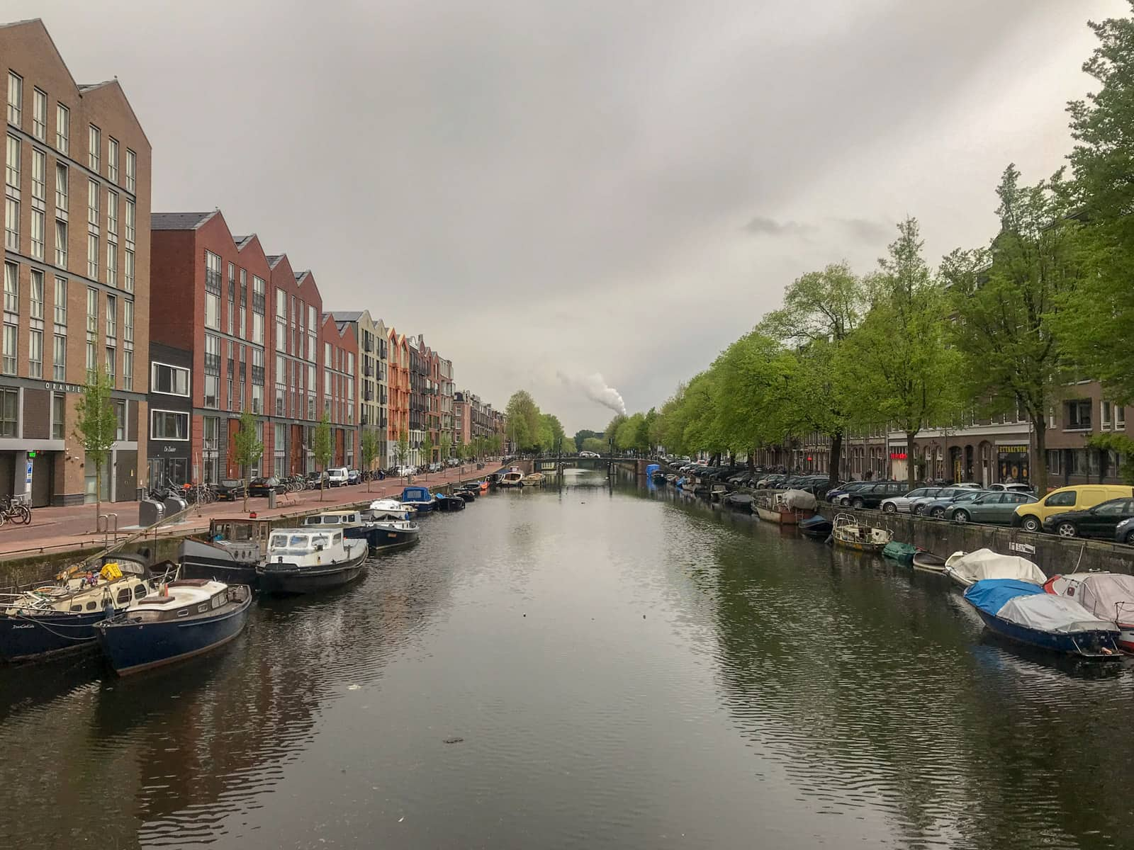 A canal in Amsterdam, seen from a bridge. The canal extends further away into the distance. Many canal boats are stationary on the sides of the canal.