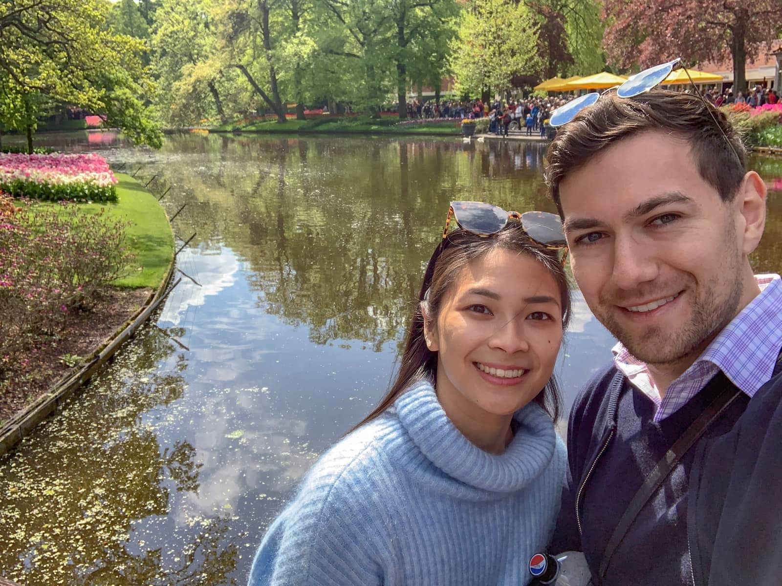 A man and woman smiling and taking a selfie in front of a river with several leafy debris in it. On the banks of the water are rows of planted tulips in bright colours.