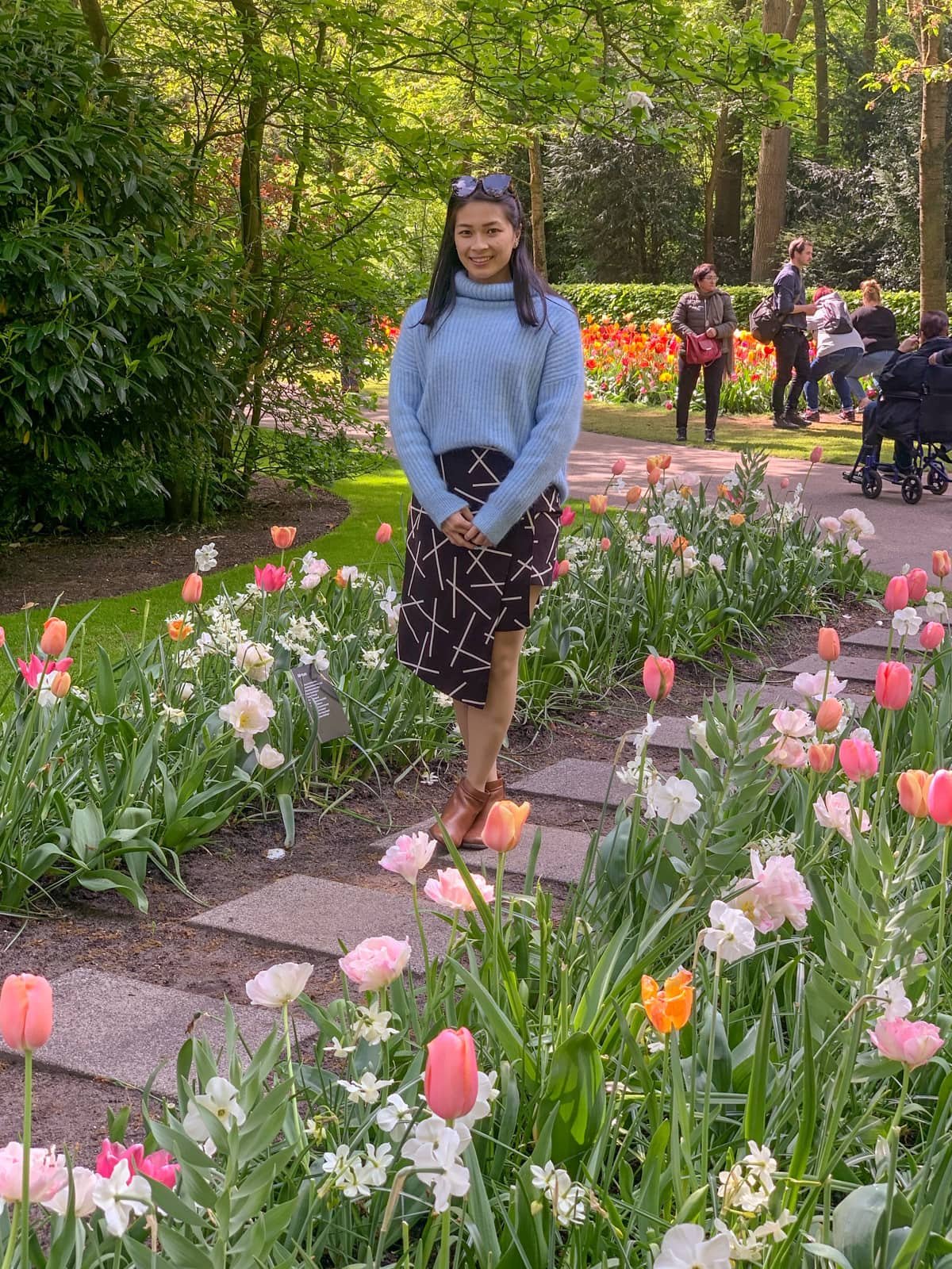 A woman in a light blue sweater and black patterned skirt standing on a square-paved stone path between two rows of tulips that are all pastel pink, orange, and yellow in colour