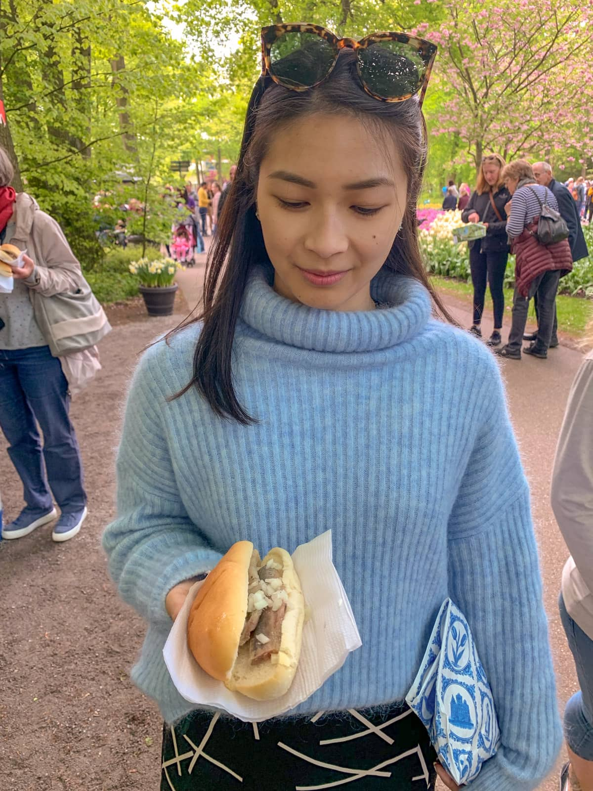 A woman wearing a light blue sweater, holding a napkin with a bun filled with raw herring and onion. She is looking down slightly at the bun with a small smile