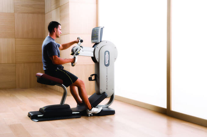 A man sitting on an ergonomic arm cycle machine with his hands in the pedals.