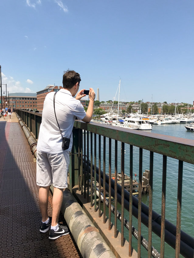A man in shorts and a white shirt, taking a photo on a camera over the railing of a bridge. He is photographing some boats in a harbour