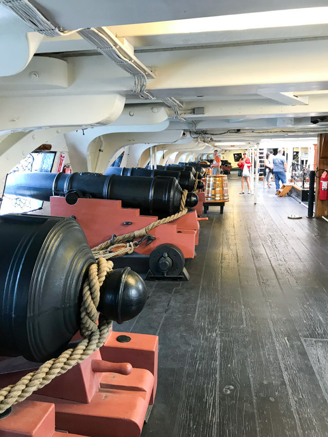 The interior of a ship, with low ceilings. There are black cannons down the left hand side