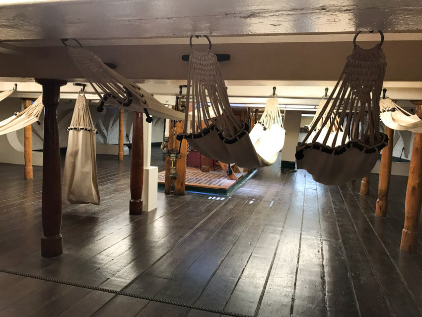 hammocks hanging from the low ceiling of the inside of a ship