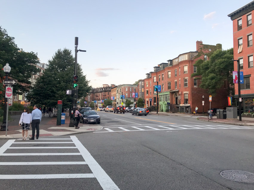 An early evening photo taken from the intersection of a street. Two crosswalks can be seen, and in the street ahead some cars can be seen as well as some historic-looking brick buildings