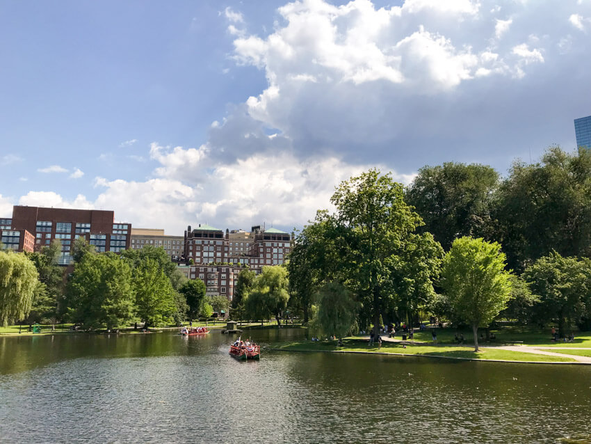 A lake in a park, filled with green trees and green grass. There is a city in the distance with brown buildings. Some boats are on the lake.