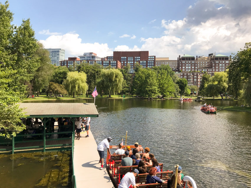 A large lake inside of a park. Down below in the foreground is a boat on the water, with wooden seats that look like benches. In the background are more of the same kind of boat. Beyond the park and its trees is a city with primarily brown buildings