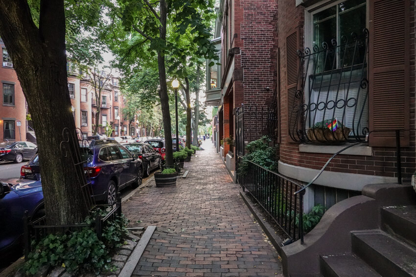 A street in the city of Boston, with adequate shade provided by the many trees on the footpath. The footpath is brick paved.