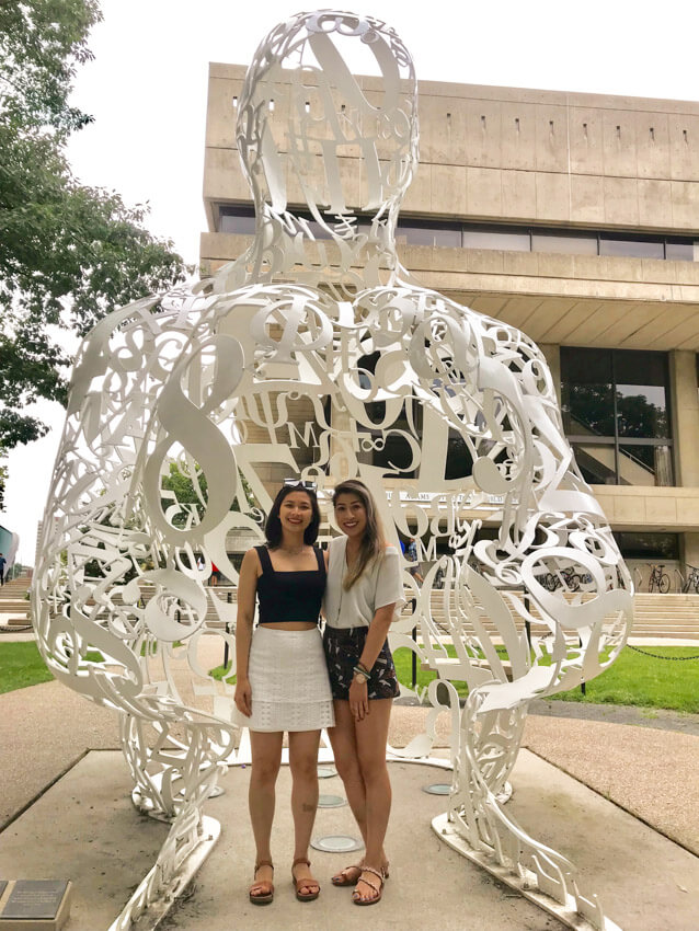 Two women, smiling, wearing summer clothing and sandals with an arm around each other. They are standing in front of a large sculpture resembling a person's head and hands, made out of white-painted steel numbers and letters