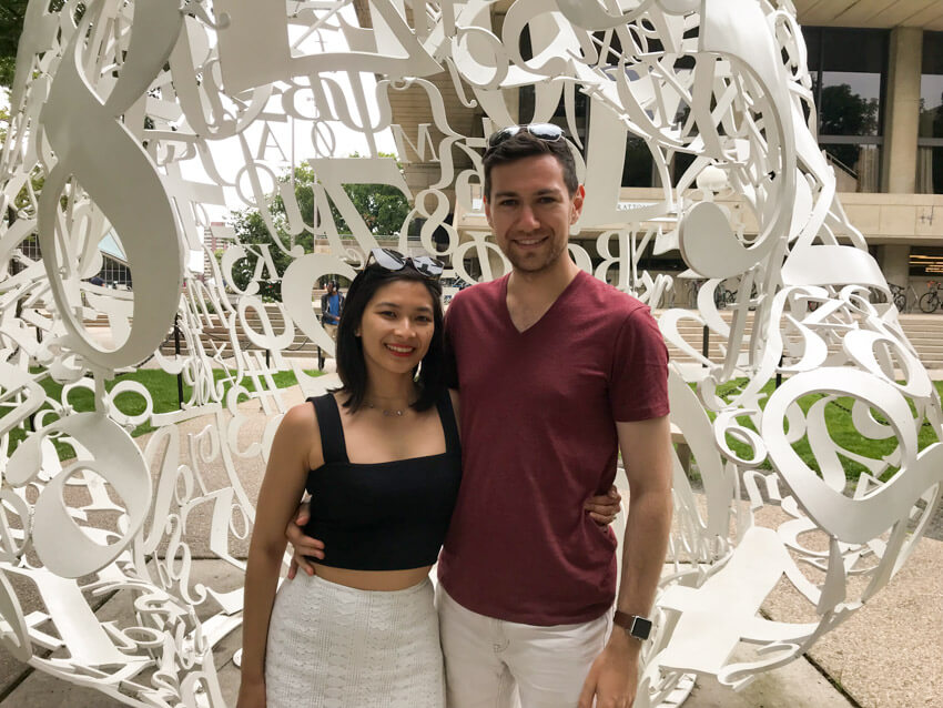 A woman and man smiling, with an arm around each other, in front of a sculpture made out of white-painted steel letters and numbers melded together