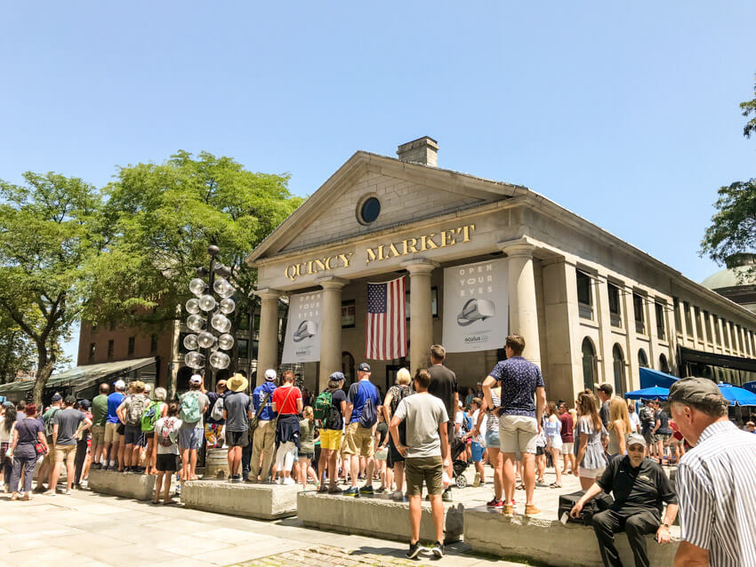 "A long building with a pillared entrance. Above the pillars are the words ""Quincy Market"". There are many people gathered around the front of the building."