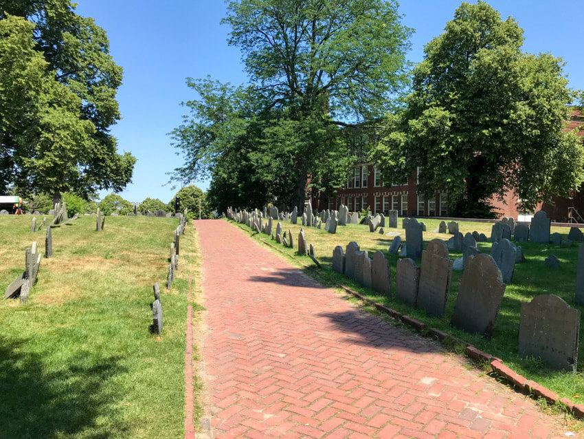 A red brick path through a cemetery, where headstones sit in lines on green grass