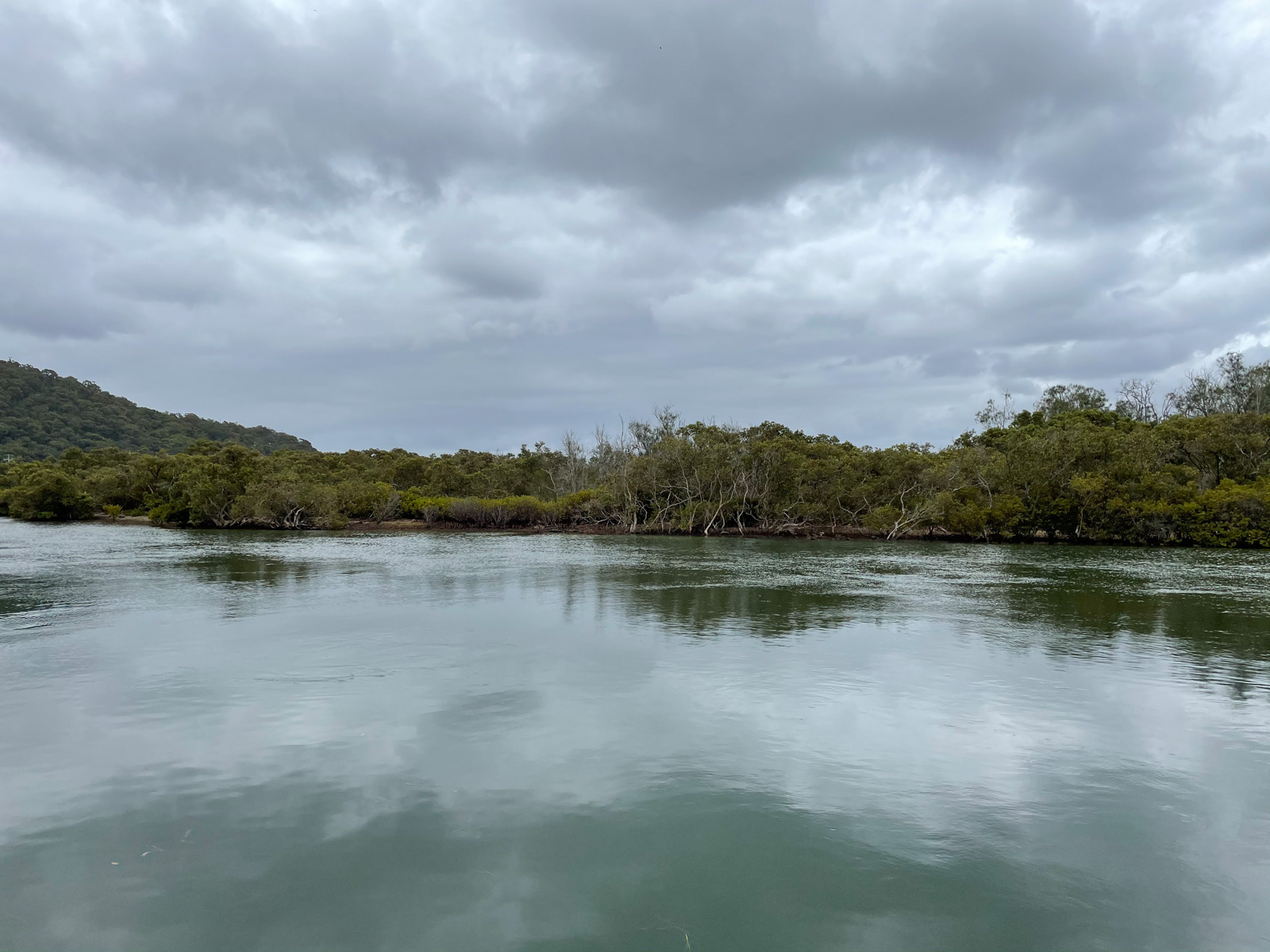 A view of a dark aqua lake with some trees on the land in the background. The sky is quite grey and cloudy, but not dark