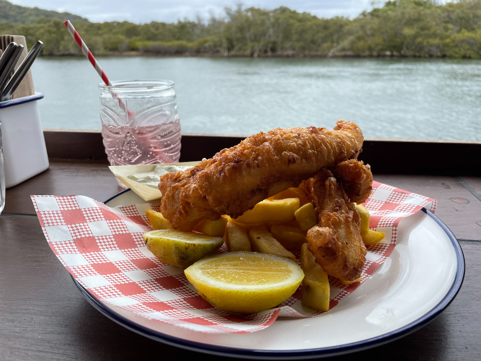 A plate of battered fish and chips on a wooden surface. Behind it is a glass with a translucent pink liquid in it. The view in the background is of a lake