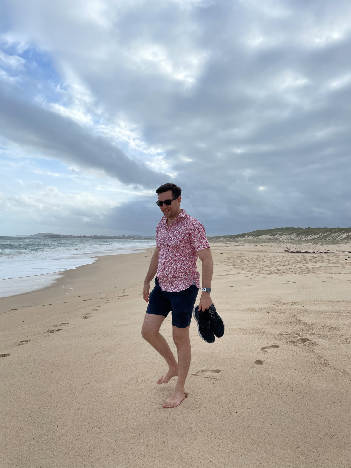 A man wearing dark sunglasses, in a red patterned shirt and dark blue shorts, standing barefoot on the sand of a beach. The sky is cloudy