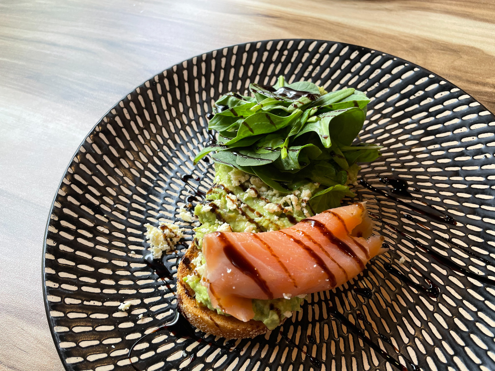 A black and white patterned plate with a slice of toast with smashed avocado spread on it, and topped with spinach, smoked salmon and balsamic glaze