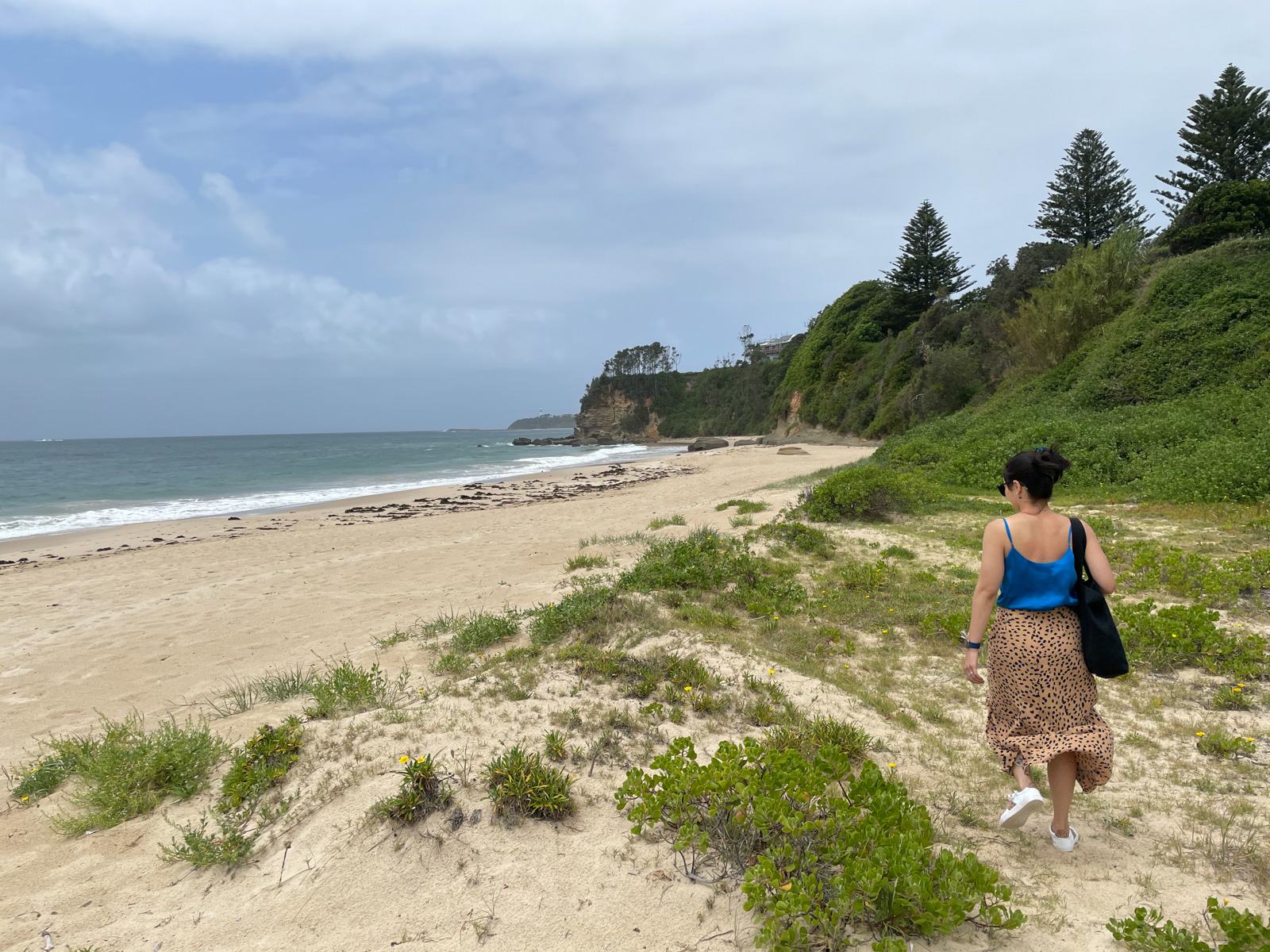A view of a beach, with grass growing out of the sand in the foreground. A woman wearing a blue top and an animal print skirt walks towards the bare sand. The sky is a bit cloudy.