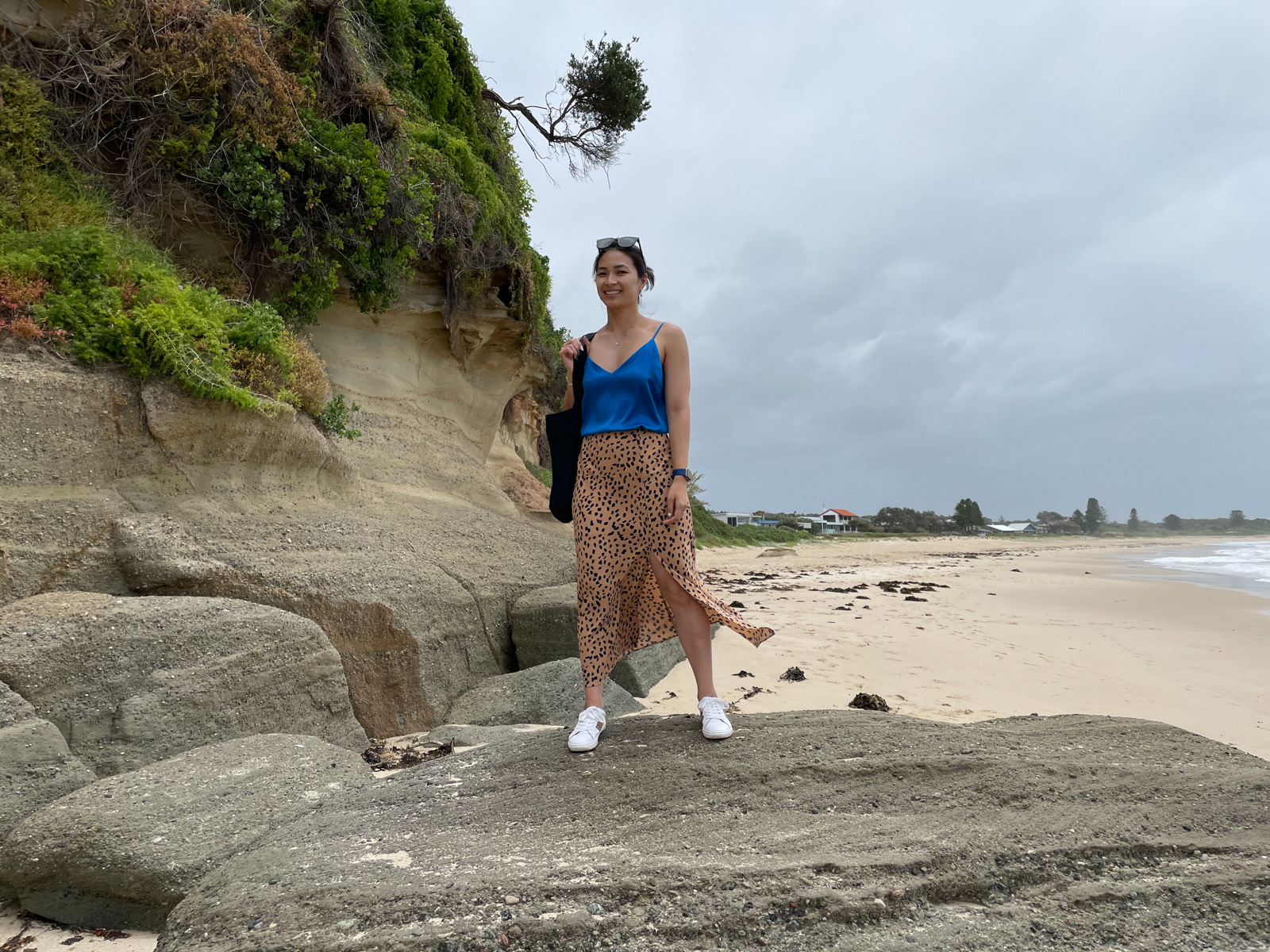 A woman wearing a blue top, animal print skirt and white shoes, standing on a giant rock on a beach. She is smiling and carrying a black tote bag, and wearing sunglasses on top of her head. The sky looks a little grey and cloudy.