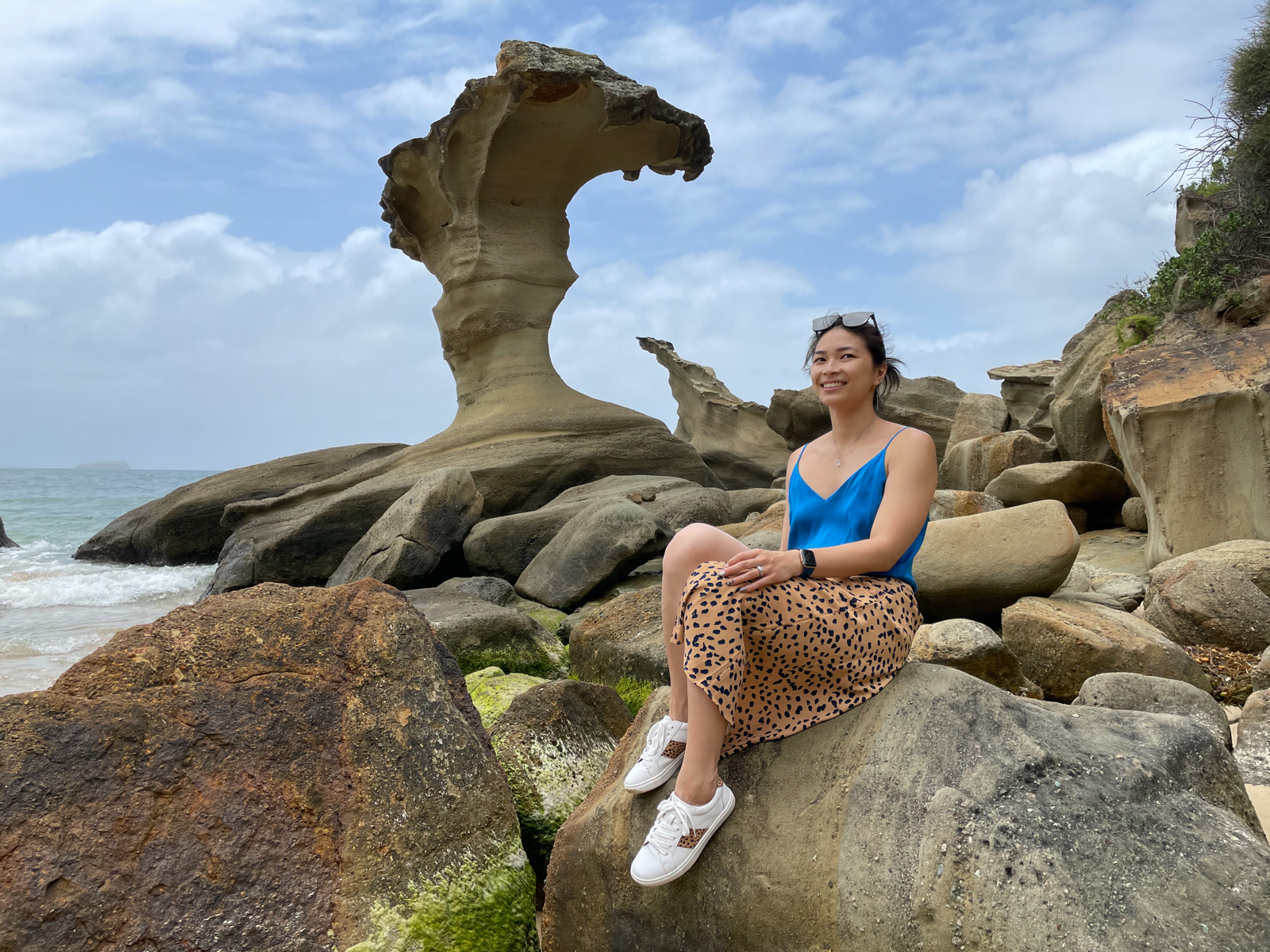 A woman sitting on a giant rock on a beach, with a wave-shaped rock formation behind her. She is wearing sunglasses on top of her head and is dressed in a blue singlet top, animal print skirt, and white sneakers.