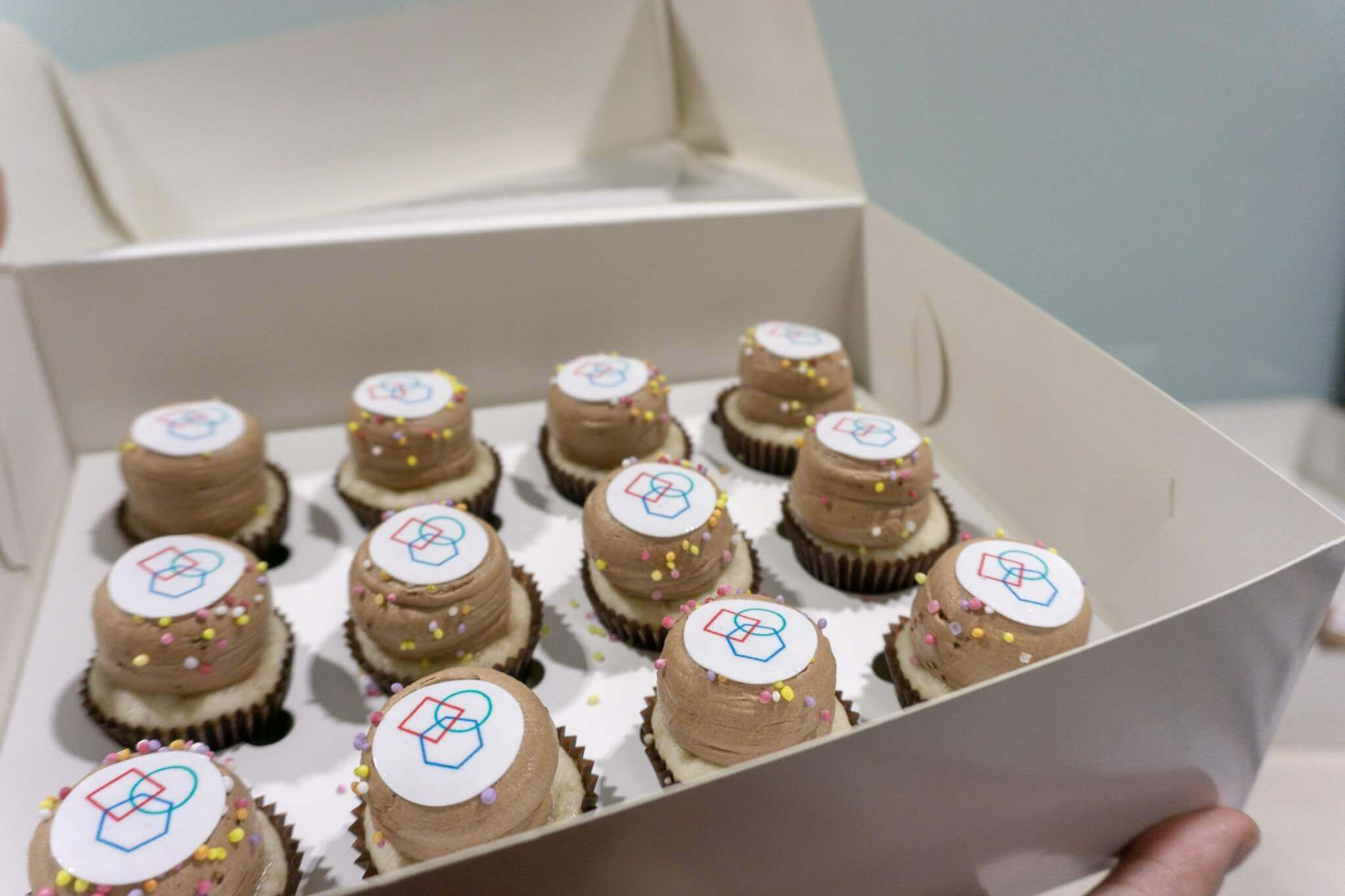 A white cardboard box with twelve miniature cupcakes. They are brown and on top have a circle with a logo on it. The logo is comprised of the overlapping outlines of shapes