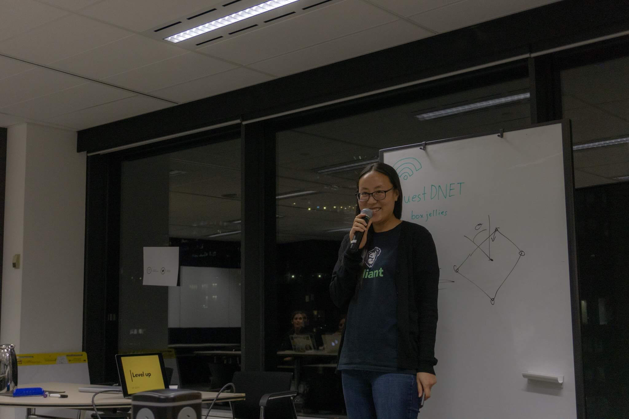 A woman wearing glasses, holding a microphone, standing next to a whiteboard
