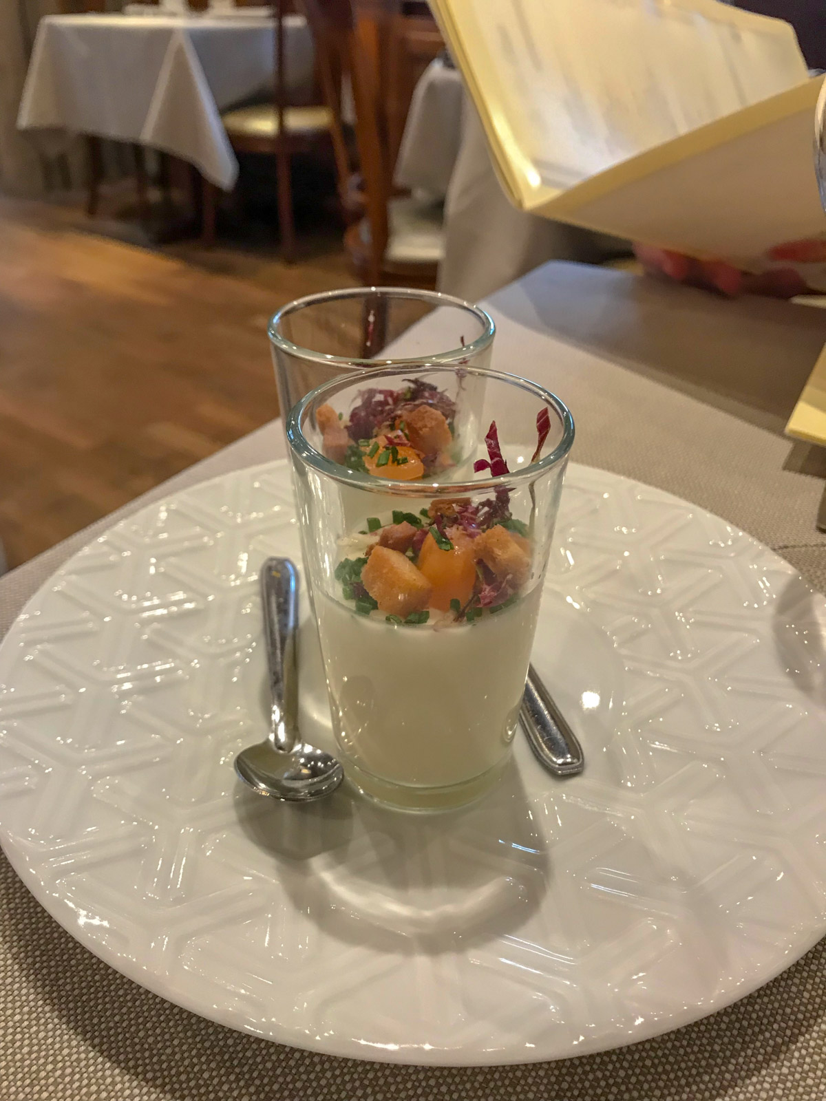 Two small glasses on a white plate, each with a small amount of white pudding and topped with raw salmon and croutons
