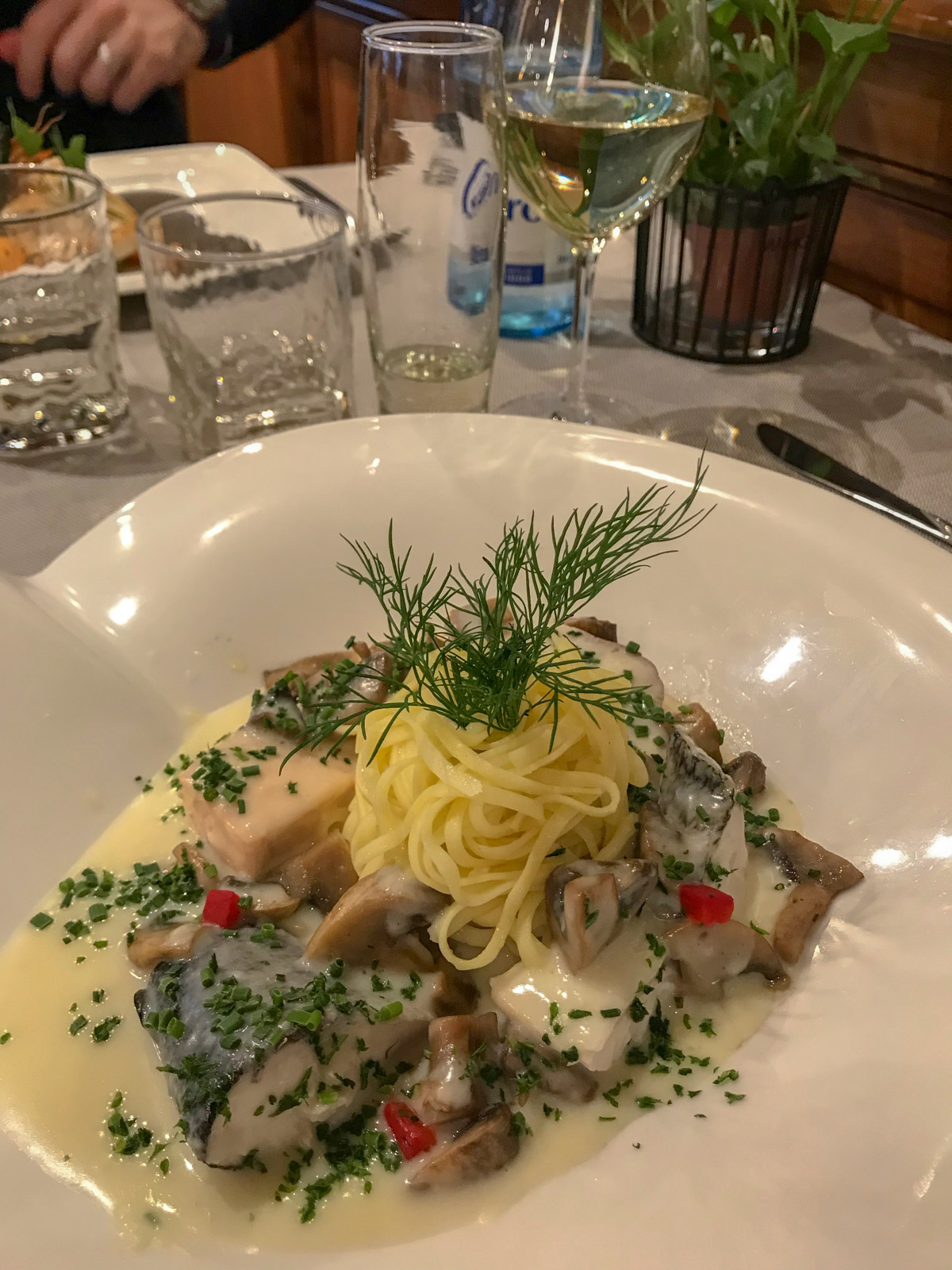 A shallow white dish with cooked fish and a ball of spaghetti, garnished with herbs and served with white sauce