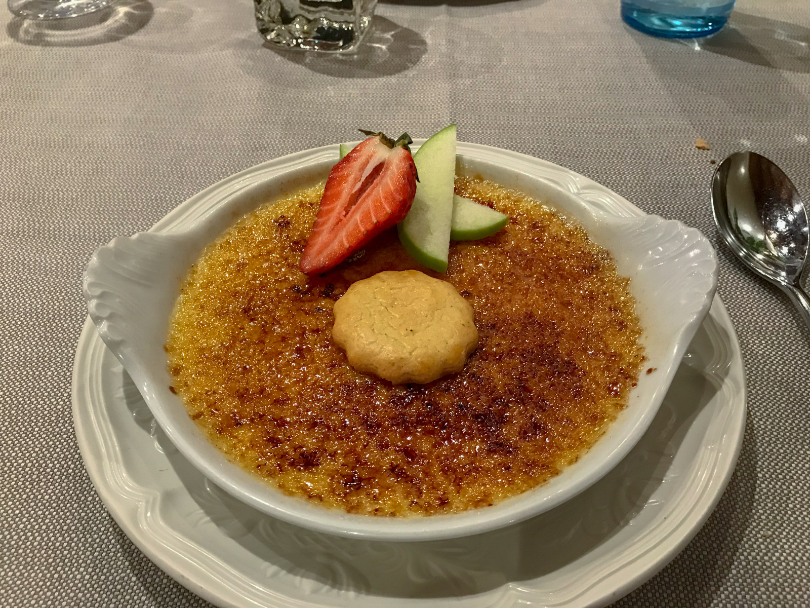 A white dish with creme brûlée served on it, topped with a couple of fruits