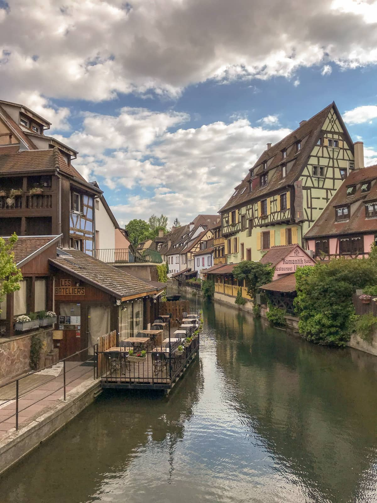A view of a river going between two banks where old, colourful houses are erected, in the city of Colmar, France