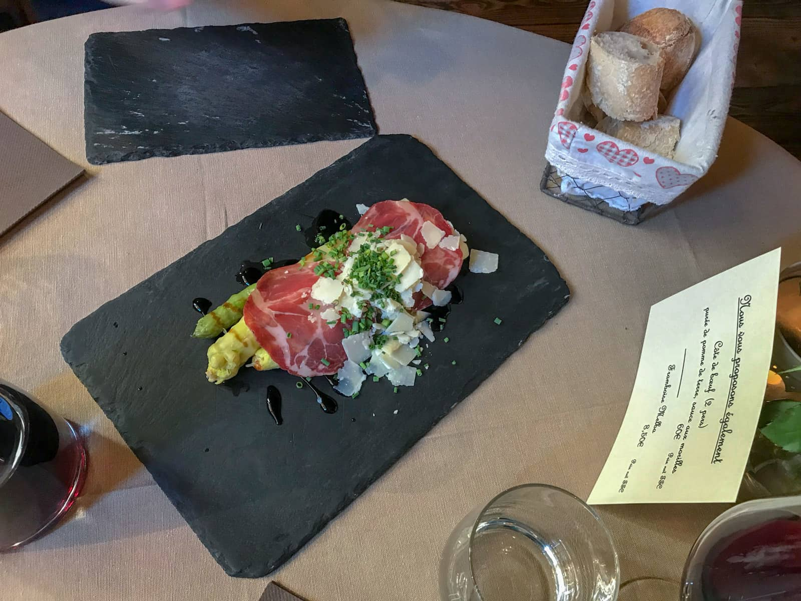 Asparagus with a slice of proscuitto and shaved cheese, presented on a black stone board on a dinner table in a restaurant