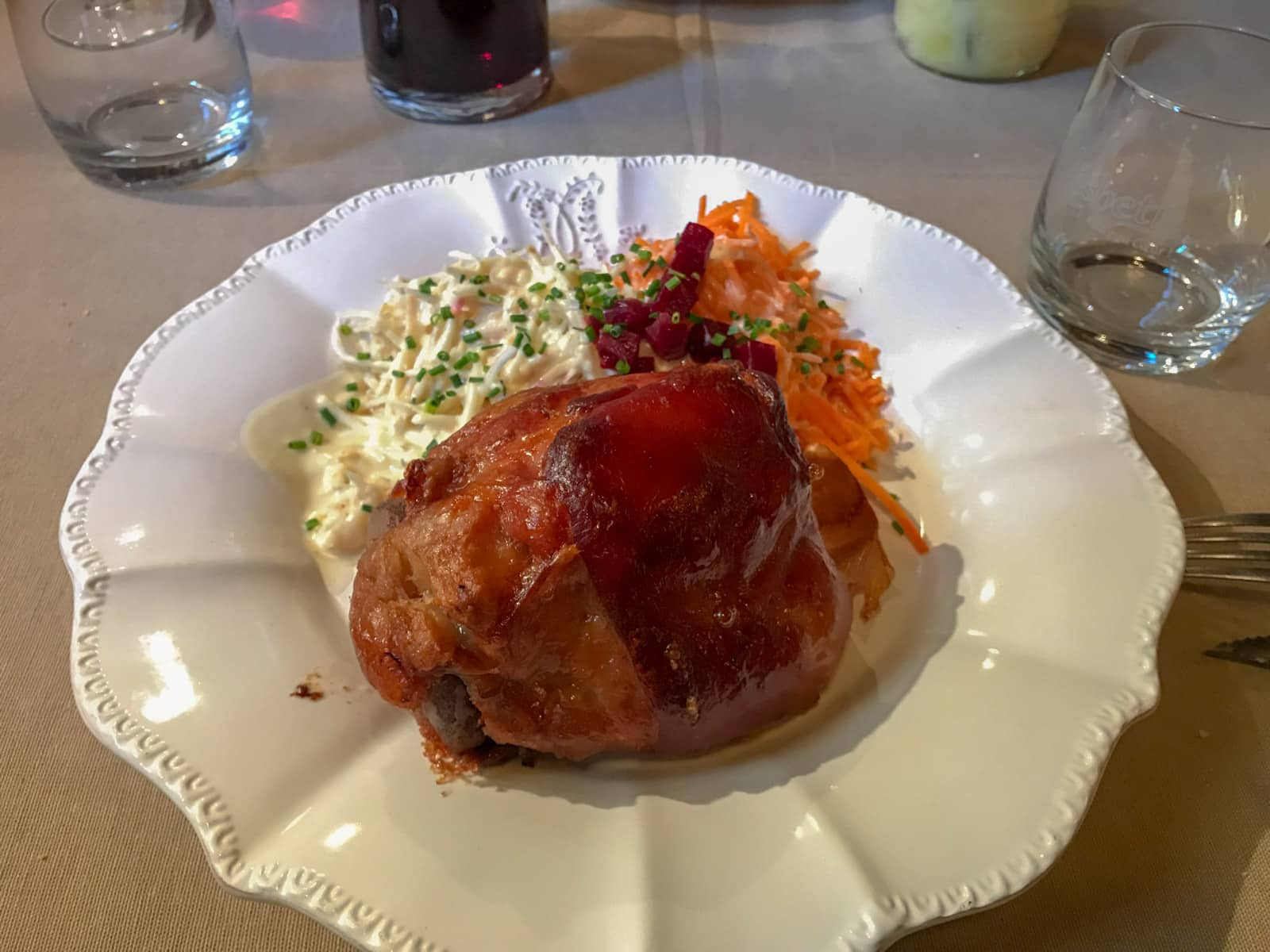 A white plate with pork knuckle and cabbage salad served on it